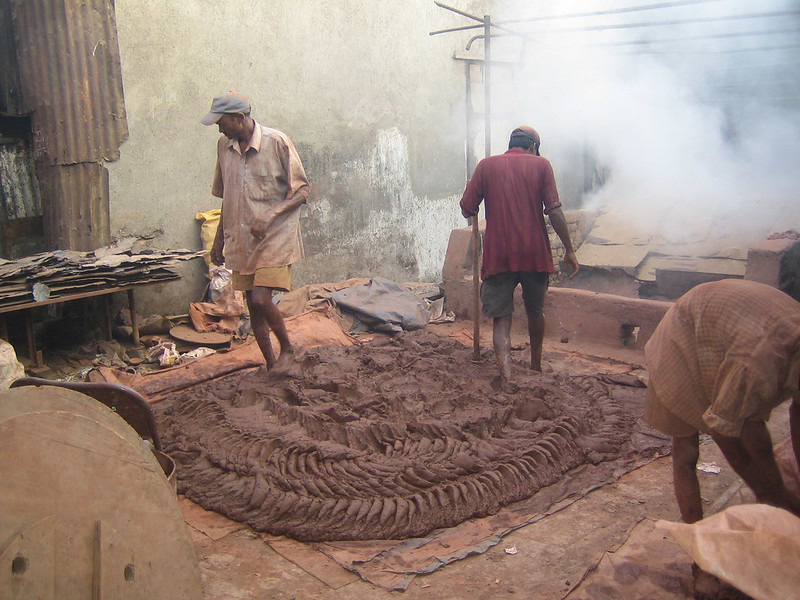 The clay is kneaded with feet to achieve a smooth consistency.