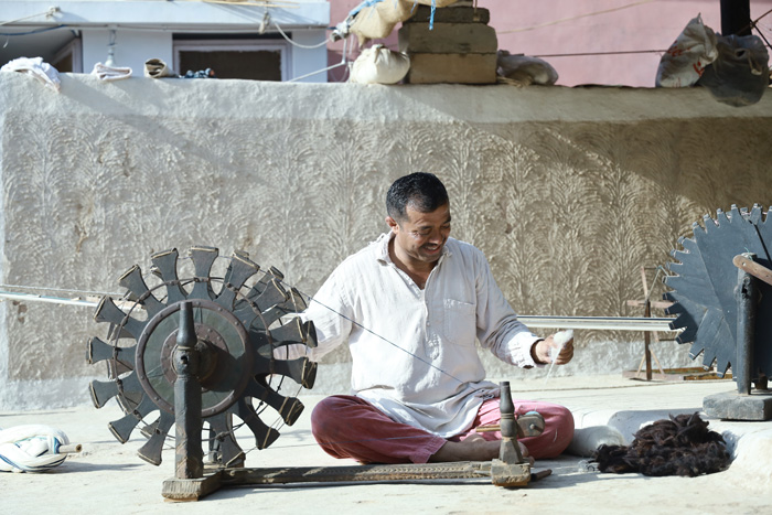 The process starts with spinning the raw wool fibres or cotton on the traditional wooden wheel (charkha) to make yarn.  Shamji Valji still uses the traditional wooden charkha (spinning wheel) even now.  Pic: Shamji Valji  30 stades