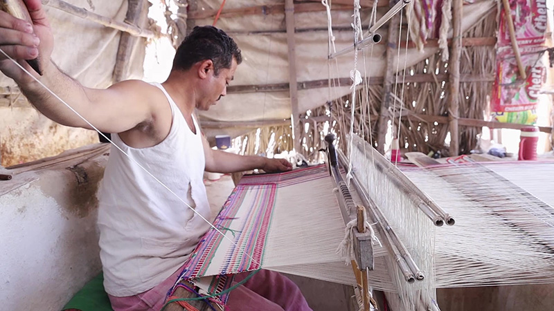 The yarn is put on the warp (tano) on the loom. Weaving is done on a pit loom, where the weaver's feet are below the loom while he sits at the ground level, giving it the name of pit loom.  Pic: Shamji Valji  30 stades