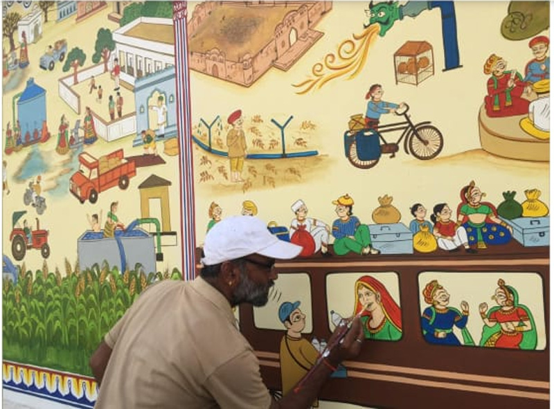 Kalyan Joshi painting on a wall to create awareness around water conservation.