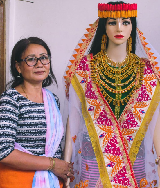 Shrimayum Gita Devi stands with a mannequin sporting cocoon headgear, earrings and necklace. Pic: Leima Liklang Nayin