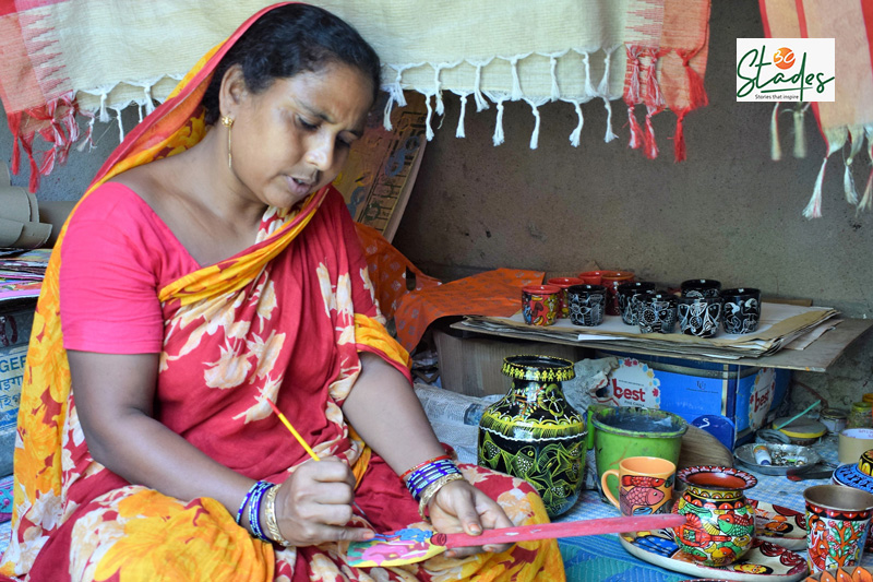 Putul Chitrakar continues to sing songs with her Patachitra scrolls even today. Painting a wooden ladle here. Pic: Partho Burman