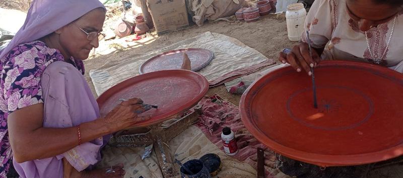 Women painting on the pottery which has been quoted with geru (reddish colour). Pic: Abdulbhai 30 stades khavda pottery
